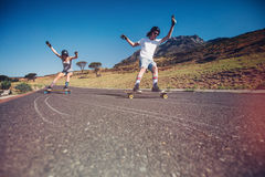 Young couple skateboarding on the road Stock Photos