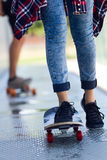 Young couple skateboarding in the street. Stock Photos