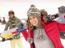 Young Couple On Ski Vacation. Smiling and woman holding a pair of skis royalty free stock photography