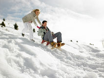 Young Couple Sledding Royalty Free Stock Photo