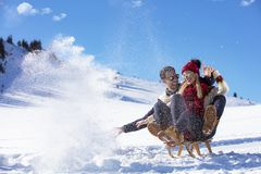 Young Couple Sledding And Enjoying On Sunny Winter Day.  Royalty Free Stock Photos