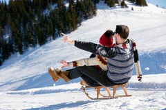 Young Couple Sledding And Enjoying On Sunny Winter Day Royalty Free Stock Images