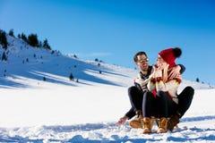 Young Couple Sledding And Enjoying On Sunny Winter Day Stock Photo