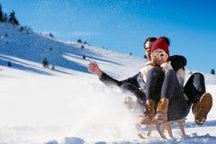 Young Couple Sledding And Enjoying On Sunny Winter Day Stock Images