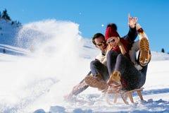 Young Couple Sledding And Enjoying On Sunny Winter Day Stock Image