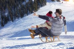 Young Couple Sledding And Enjoying On Sunny Winter Day.  Royalty Free Stock Images