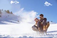 Young Couple Sledding And Enjoying On Sunny Winter Day.  Stock Photography