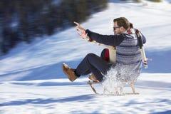 Young Couple Sledding And Enjoying On Sunny Winter Day.  Stock Photo