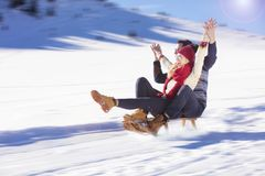 Young Couple Sledding And Enjoying On Sunny Winter Day.  Royalty Free Stock Image