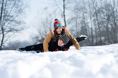Young couple sledding on snow. Winter collection: winter fun, young couple jumping outdoors Royalty Free Stock Images