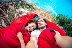Young couple in sleeping bags near the sea. Young couple lying in red sleeping bags near the sea Stock Image