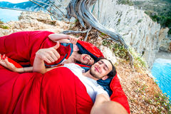 Young couple in sleeping bags near the sea. Young couple lying in red sleeping bags near the sea Royalty Free Stock Photo