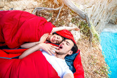 Young couple in sleeping bags near the sea. Young couple lying in red sleeping bags near the sea Royalty Free Stock Photography