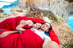 Young couple in sleeping bags near the sea. Young couple lying in red sleeping bags near the sea Stock Photography