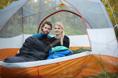 Young Couple With Sleeping Bags In Tent. Portrait of young couple with sleeping bags in tent at forest Stock Photos