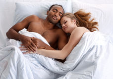 Young couple sleeping on the bed in bedroom. Concept of cheerful American family Stock Photography