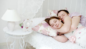 Young couple sleeping on the bed. Embracing young couple sleeping on the bed Royalty Free Stock Photography