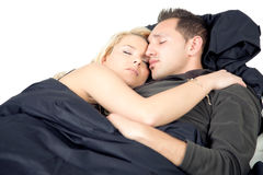 Young couple sleeping in bed. Entwined in each others arms as they enjoy happy dreams and a restful sleep Stock Images