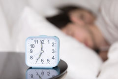 Young couple sleeping in bed next to an alarm clock Stock Photos