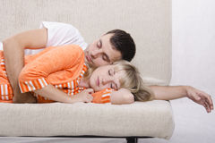 Young couple sleeping on the couch. The guy took her in his arms from behind Stock Images