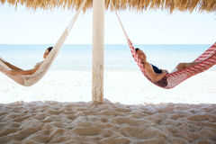 Young couple sleeping in hammocks at the beach. Profile view of a young couple sleeping in side by side hammocks during their vacation at the beach Royalty Free Stock Photos
