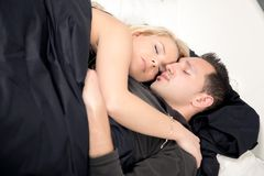 Young couple sleeping peacefully in bed. Entwined in each others arms enjoying sweet dreams Stock Photo