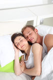 Young couple sleeping peacefully in bed. Lying close together with happy smiles as they enjoy their dreams Royalty Free Stock Image