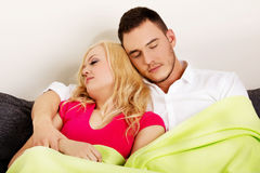 Young couple sleeping on the sofa under blanket Stock Photography