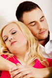 Young couple sleeping on the sofa under blanket Stock Photo