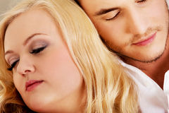 Young couple sleeping on the sofa under blanket.  Stock Photos