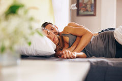 Young couple sleeping soundly in bed together. Image of young couple sleeping soundly in bed together. Husband and wife sleeping together in their bedroom Royalty Free Stock Photos