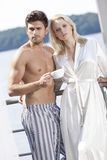 Young couple in sleepwear having coffee on hotel balcony Stock Photography
