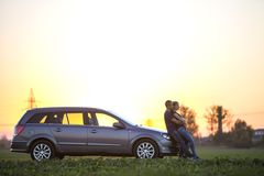 Young couple, slim attractive woman with long ponytail and handsome man standing at silver car in green field on clear sky at stock photo