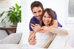 Young couple with a smartphone at home Royalty Free Stock Images