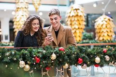 A young couple with smartphone in shopping center at Christmas. Stock Photo