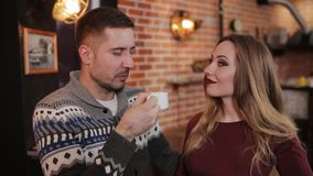 Beautiful couple at the bar in a cafe drinking coffee and talking. Young couple with smartphone talking and drinking drinking coffee in a cafe stock footage