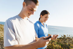 Young couple with smartphones outdoors Royalty Free Stock Photos