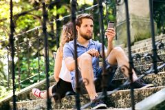 Young couple with smartphones sitting on stairs in town. Stock Photos