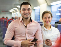 Young couple with smartphones in train Royalty Free Stock Photography