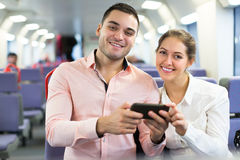 Young couple with smartphones in train Royalty Free Stock Image