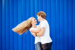 Young couple smiling on a blue background stock photography
