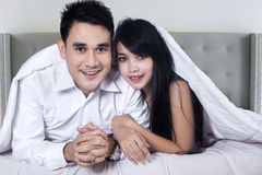 Young couple smiling at camera in hotel bedroom Stock Photos