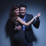 Young couple smiling in dance pose. Portrait of a young fashion couple smiling while standing in a dance pose and looking into the camera. on a dark blue Royalty Free Stock Photo