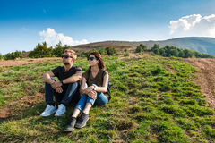 Young couple smiling, enjoying mountains lanscape, sitting on hill. Young beautiful couple in sunglasses smiling, enjoying mountains lanscape, sitting on hill Royalty Free Stock Photography