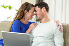 Young couple smiling face to face on sofa and using laptop Stock Photo