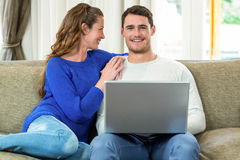 Young couple smiling face to face on sofa and using laptop Stock Image