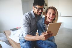 Young couple smiling and happily shopping on tablet Royalty Free Stock Images