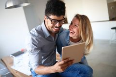 Young couple smiling and happily shopping on tablet Stock Photo