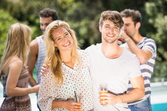 Young couple smiling and having juice together. And their friends standing behind Royalty Free Stock Photography