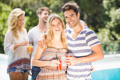 Young couple smiling and having juice together. And their friends standing behind Stock Image